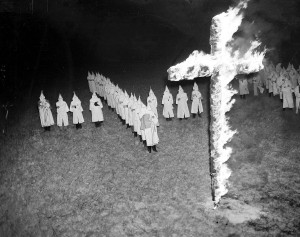 FILE - In this Jan. 30, 1939 file photo, members of the Ku Klux Klan, wearing white hoods and robes, watch a burning cross in Tampa, Fla. In 2016, KKK leaflets have shown up in suburban neighborhoods from the Deep South to the Northeast. (AP Photo/File)